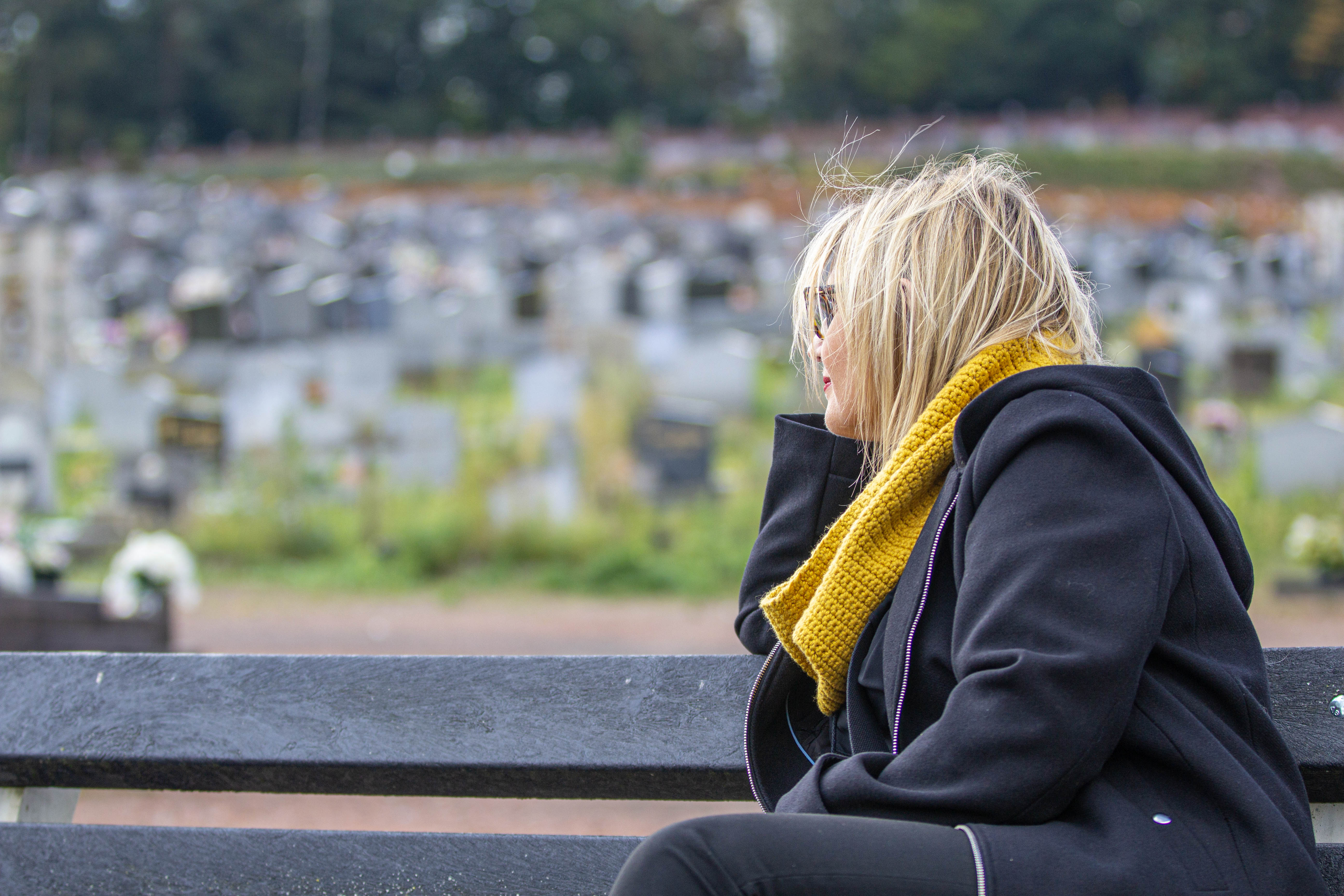 Sabine Roberty, assise sur un banc du cimetière de la Bergerie à Seraing