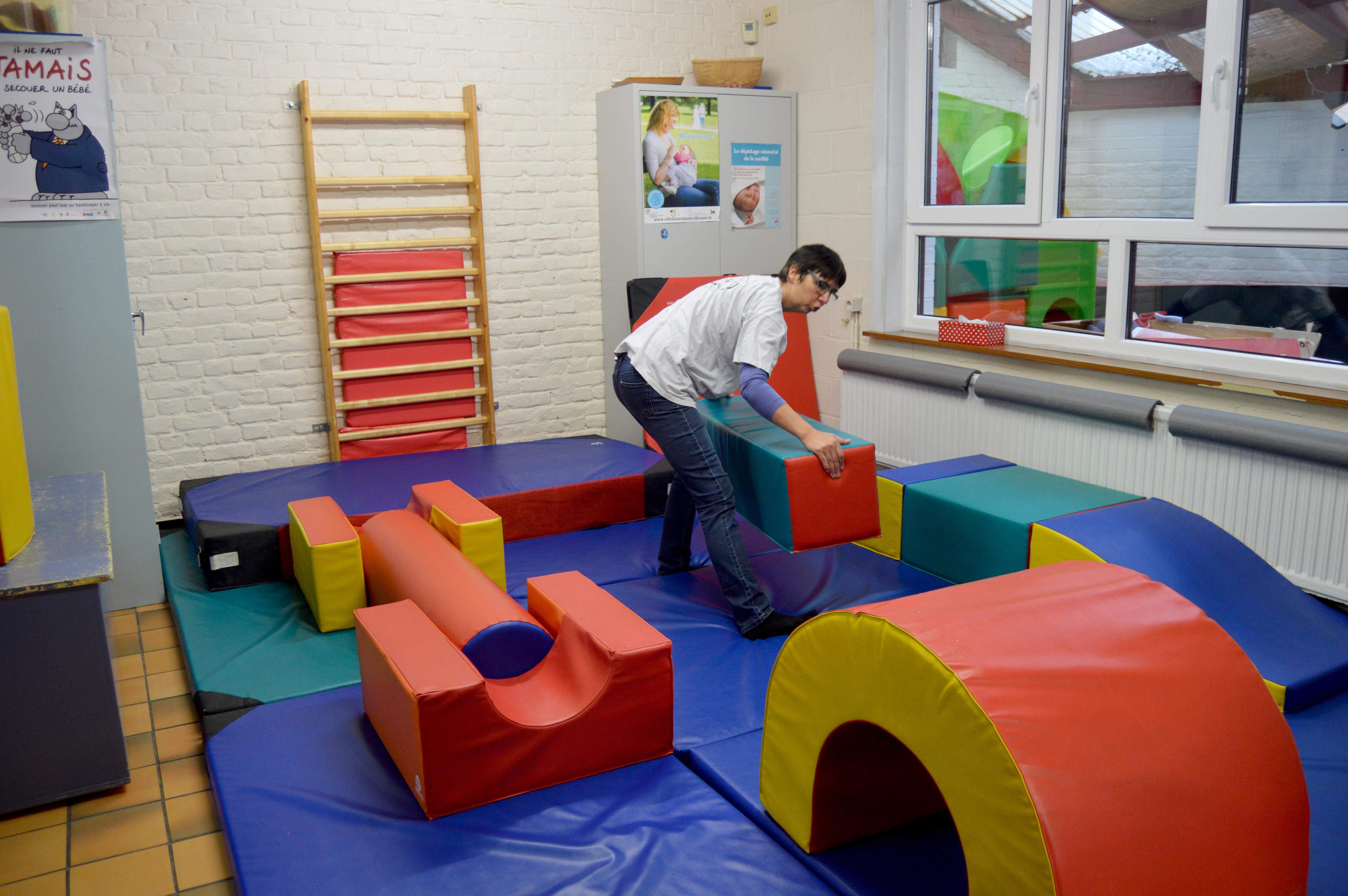 Une bénévole en train de préparer la pièce des enfants. Des toboggans, des tapis...