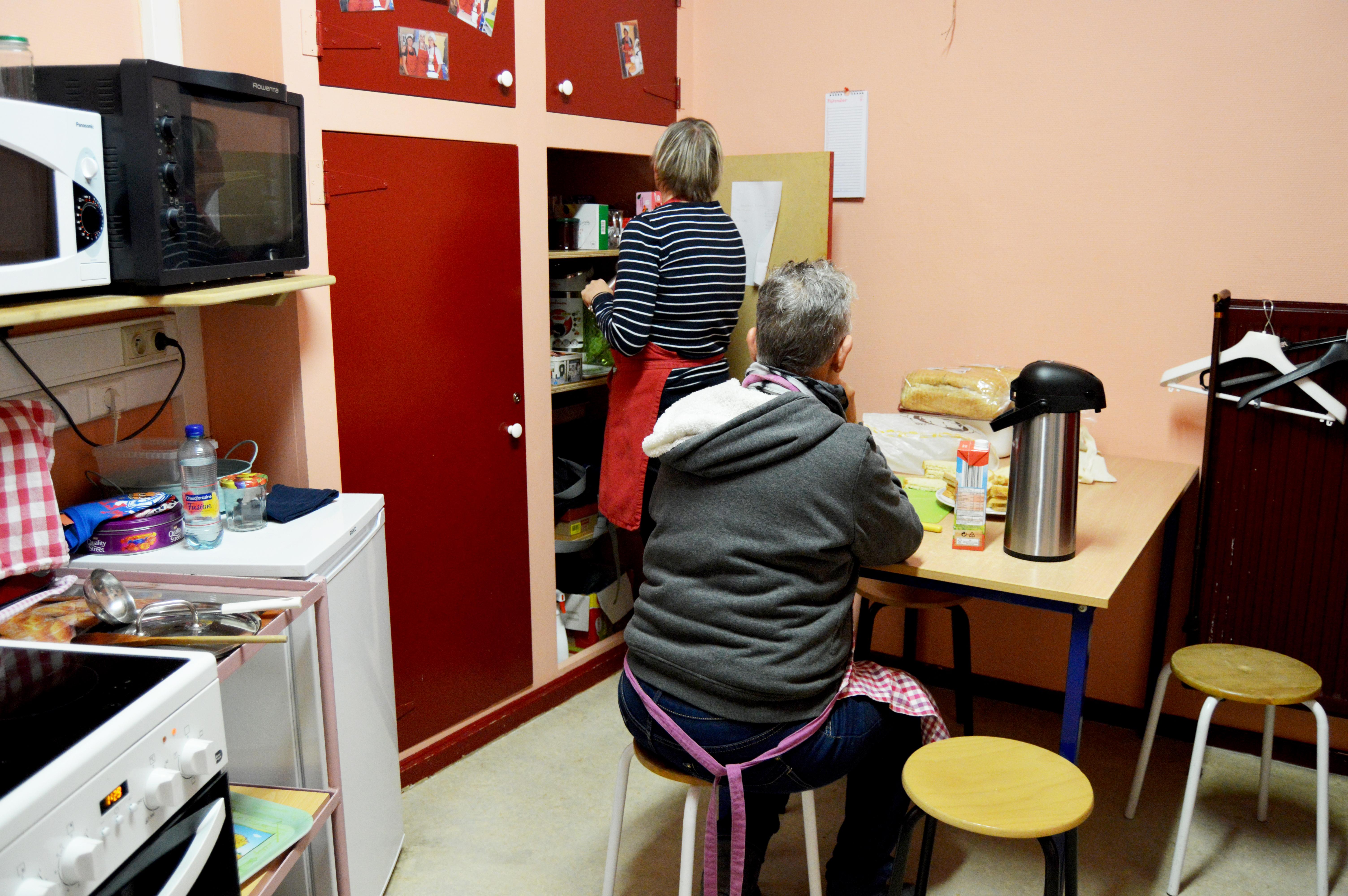 Deux personnes dans la cuisine de l'ASBL en train de préparer le potage du jour.