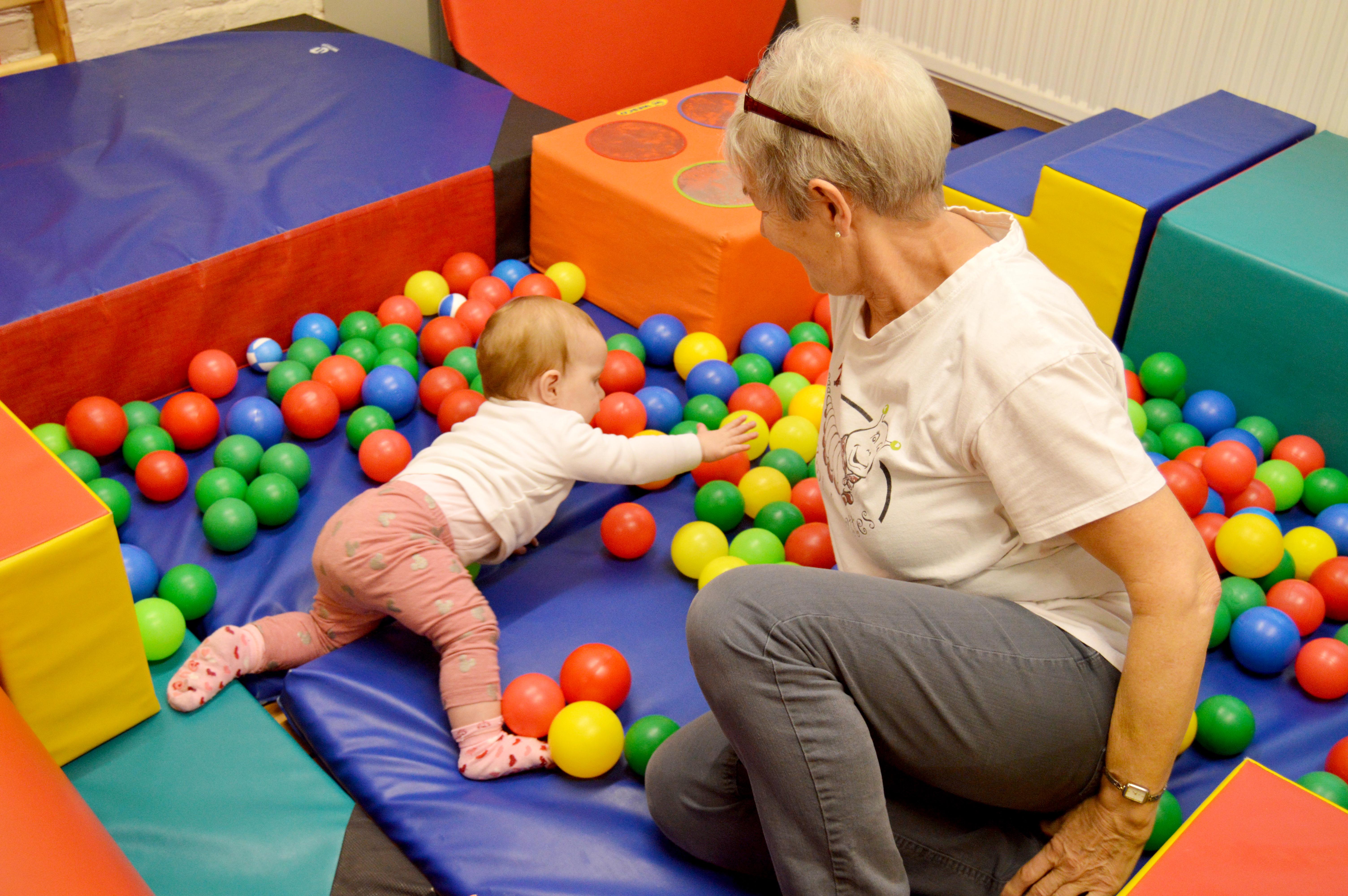 La présidente de l'association jouant avec la petite Yluna dans les balles en plastique.