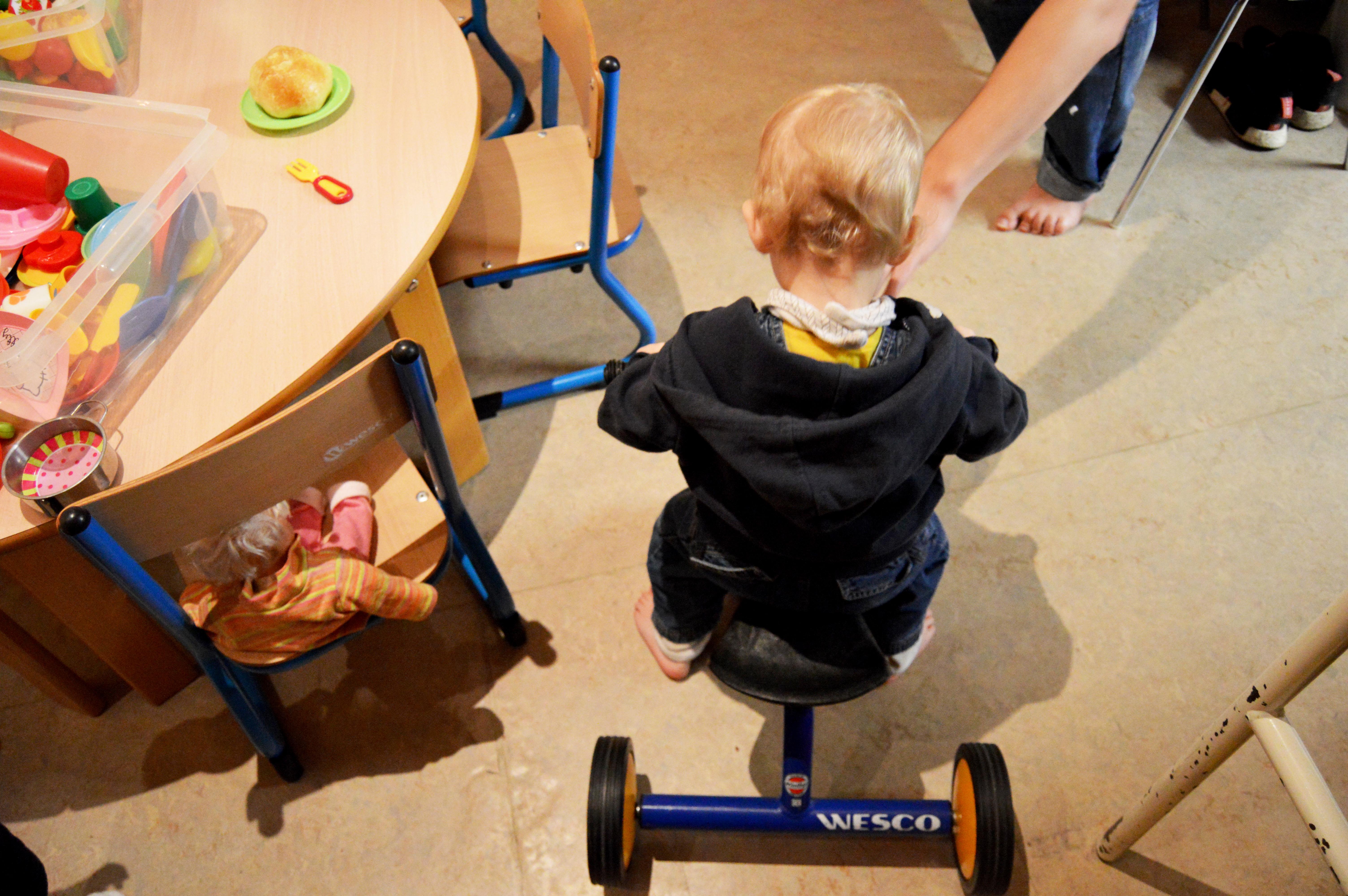 Barrath sur un petit vélo dans la pièce de la collation.