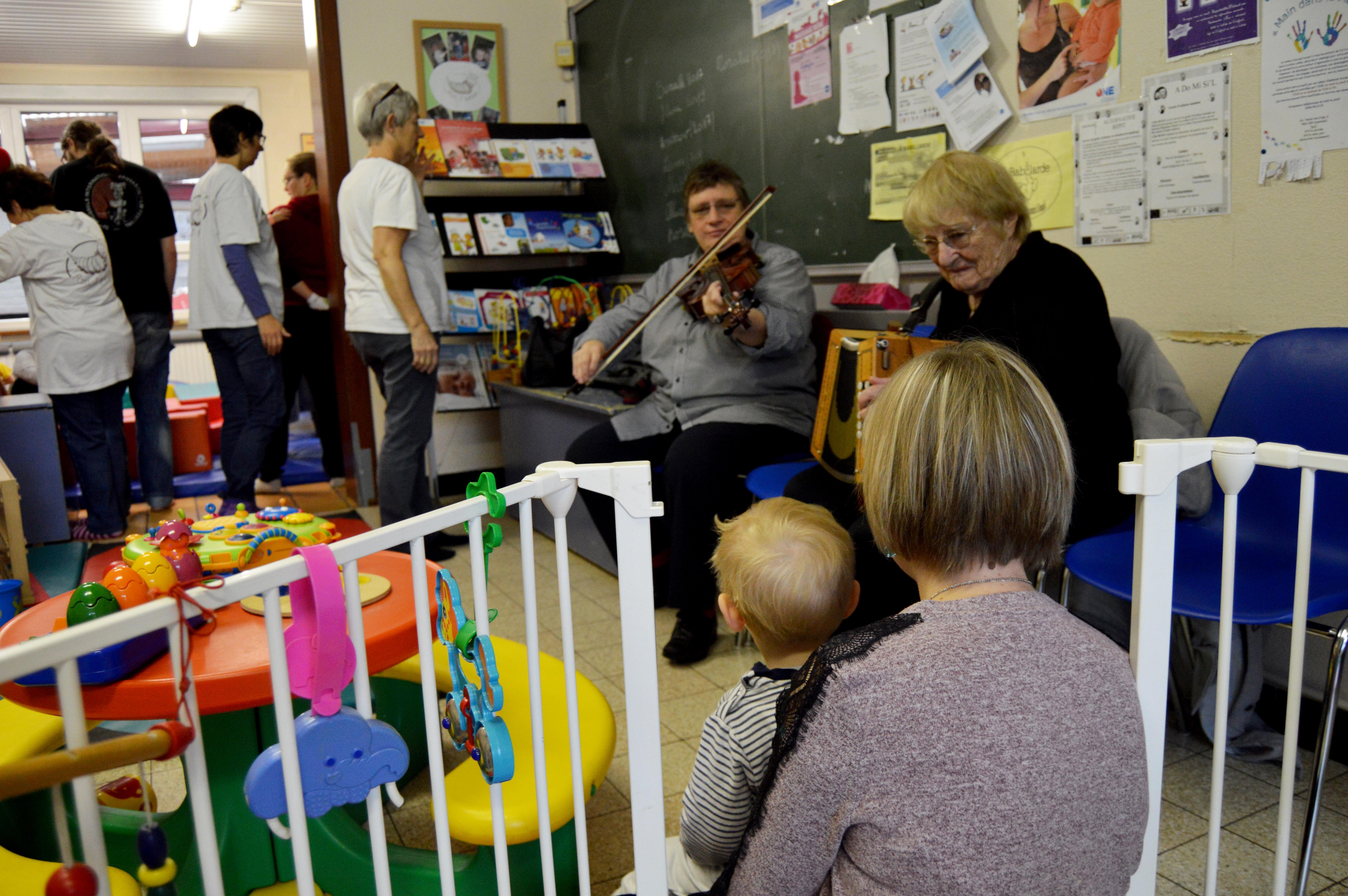 Un enfant et sa maman en train de regarder les deux musiciennes jouer.