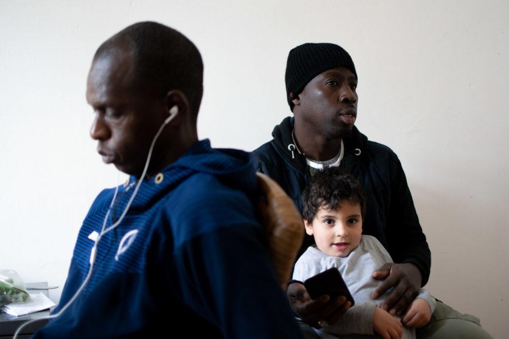 Modou tient l'enfant de son ami dans ses bras pendant qu'il discute
