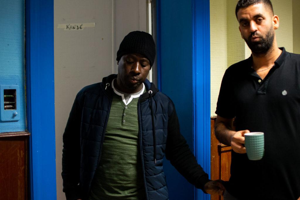 Modou et Salim discutent à la porte d'une chambre