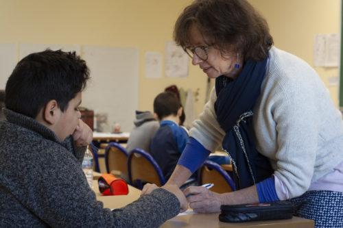 L'institutrice aide un enfant réfugié.