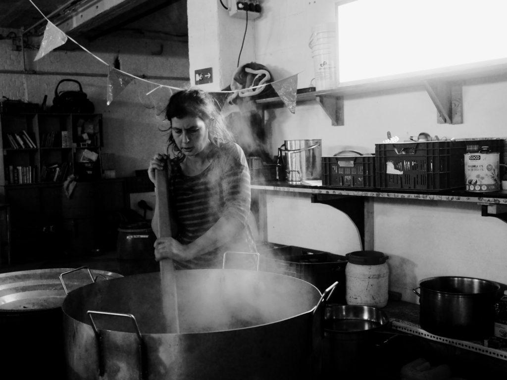 Une femme touille dans une énorme casserole
