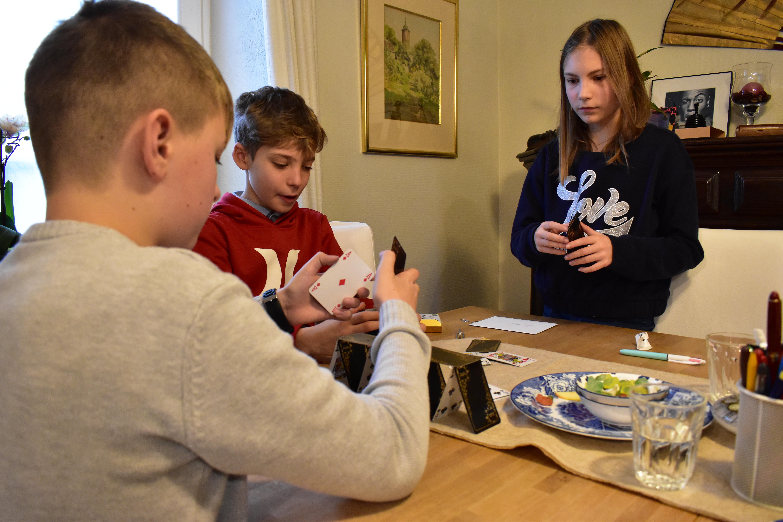 3 jeunes faisant un chateau de cartes