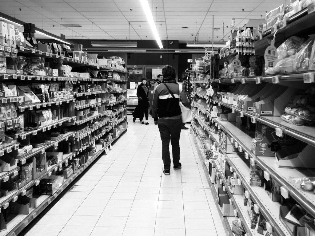 Une homme fait ses courses dans des rayons vides