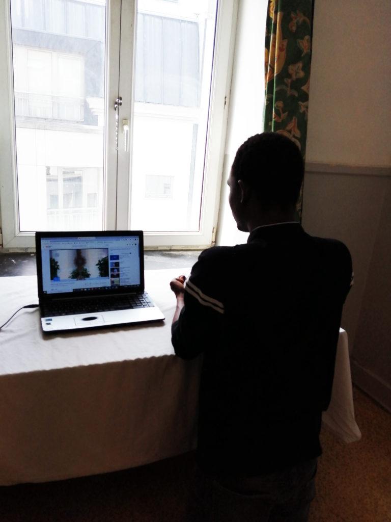 Jeune étudiant en adoration devant son ordinateur