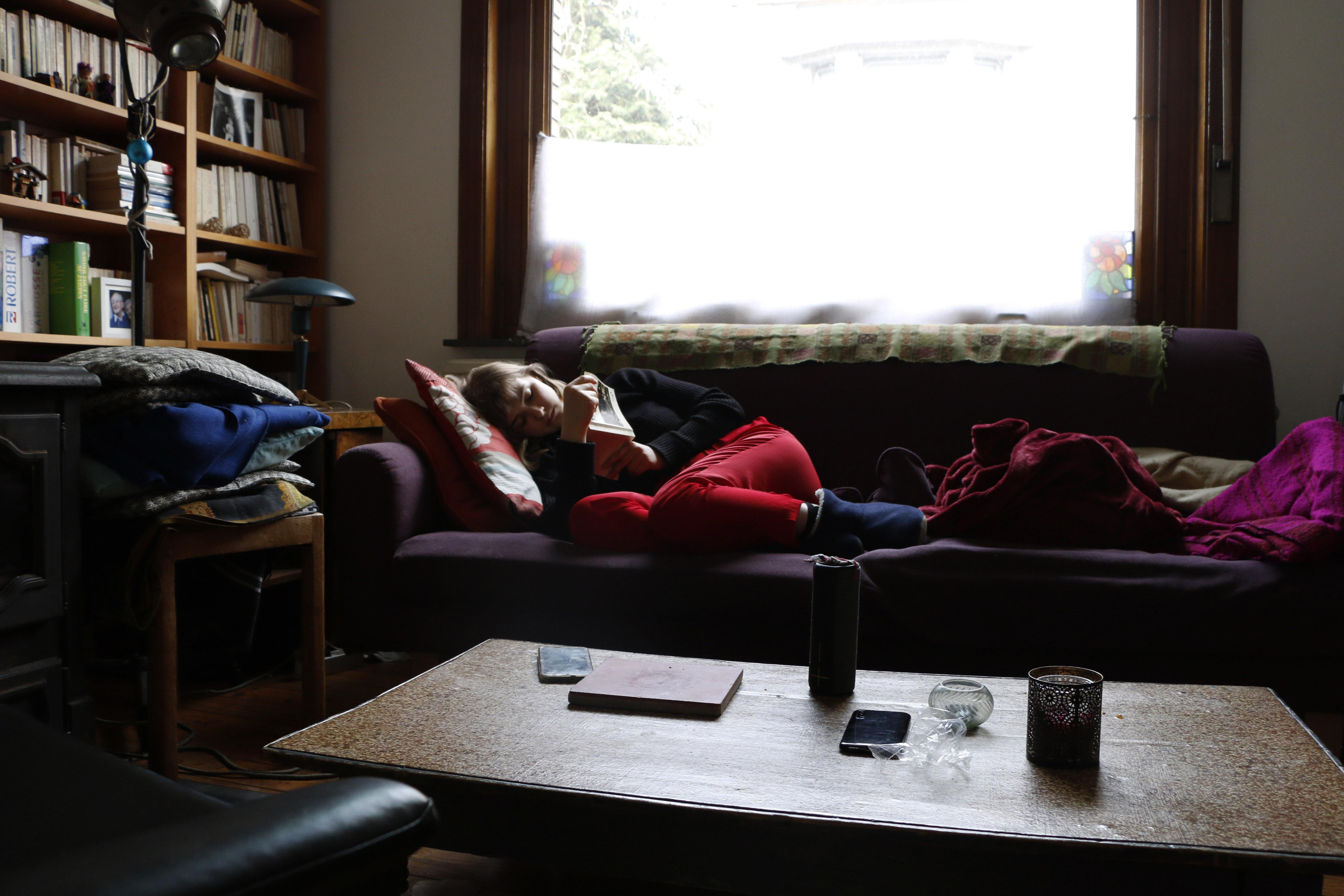 """Une jeune fille lit la pièce de théâtre """"L'Echange"""" de Claudel dans son canapé."""