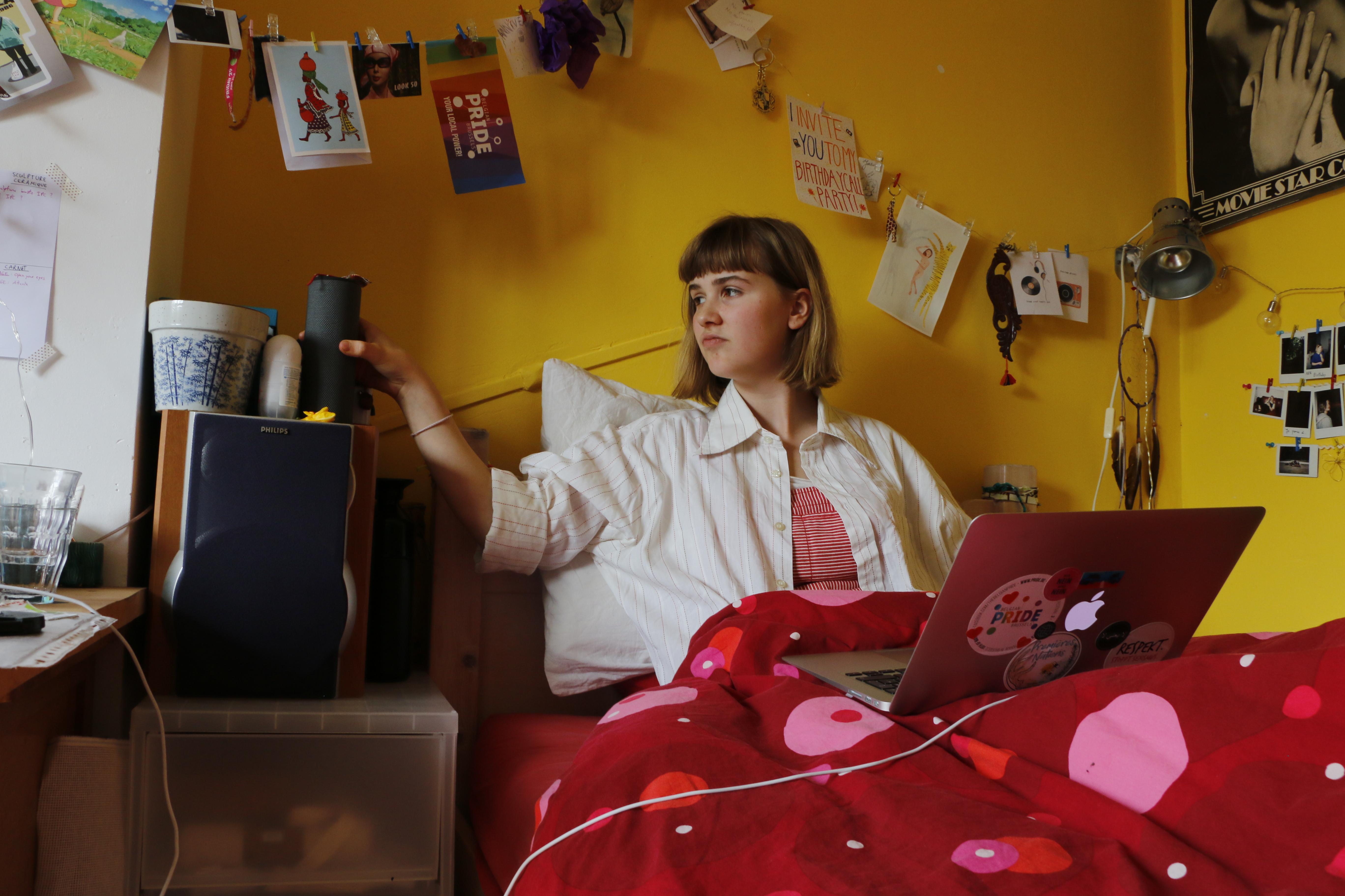 Une jeune fille regarde un concert assise dans son lit.