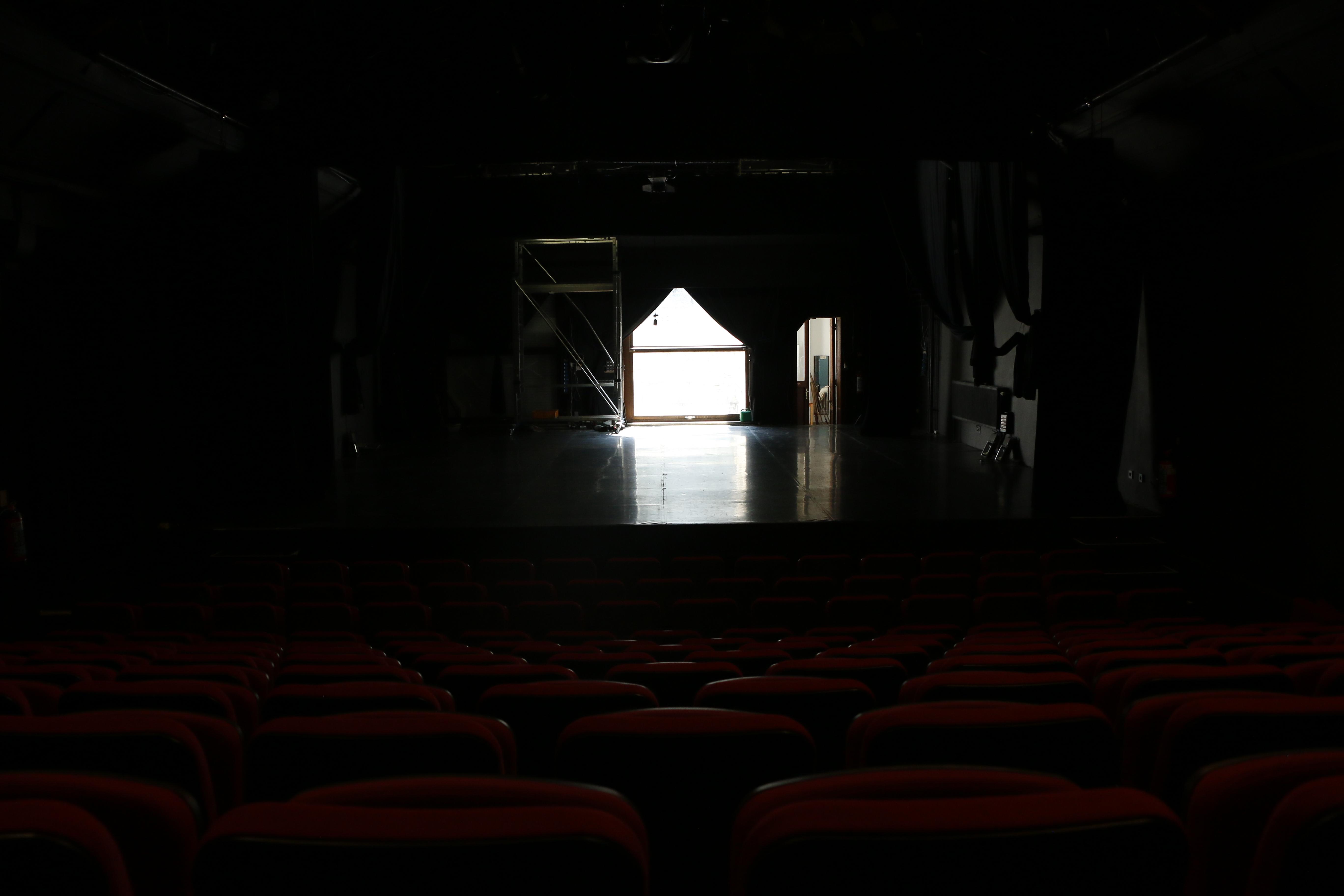 Salle de théâtre vide avec une fenêtre derrière la scène qui rappelle la forme d'une maison.
