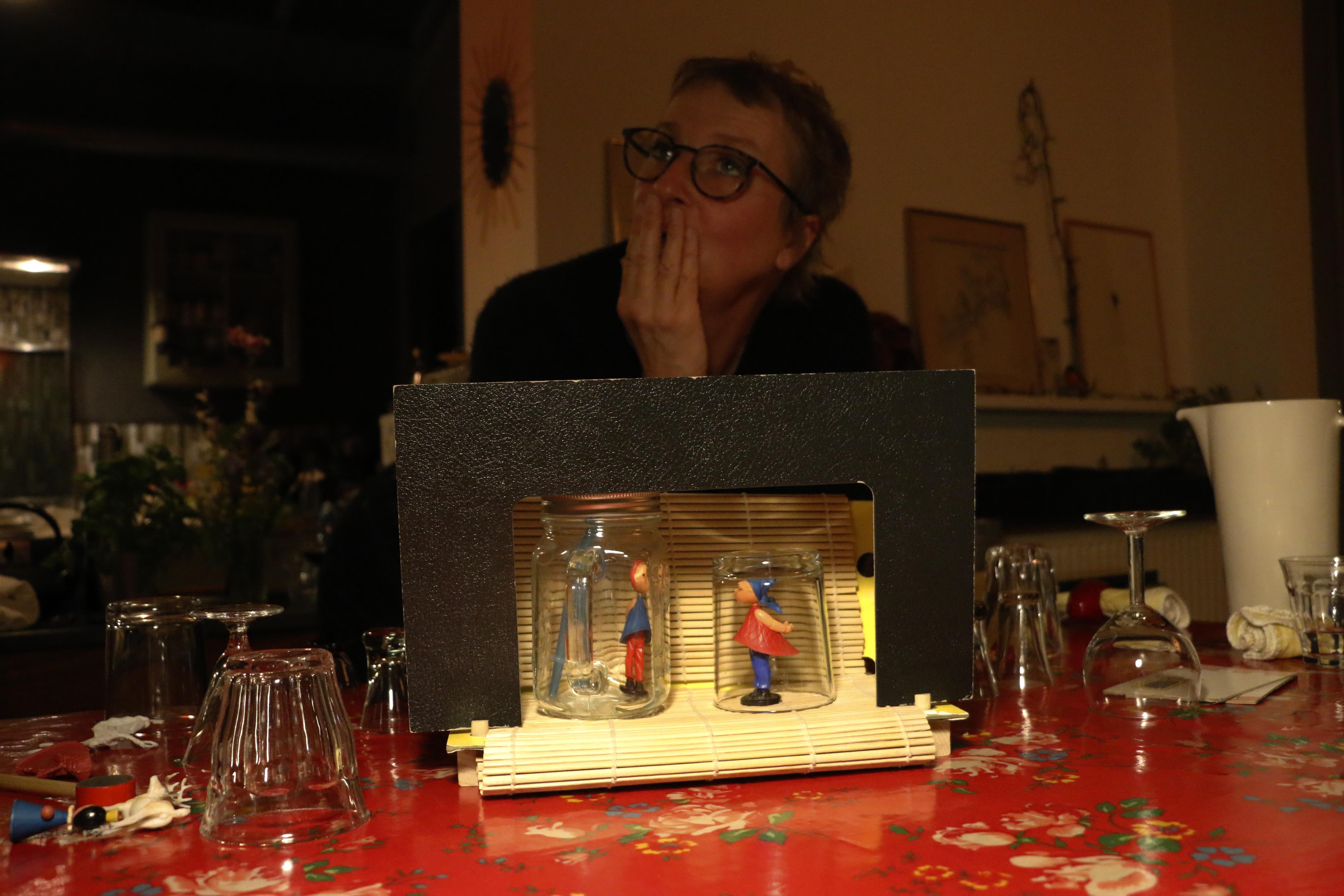 Un petit théâtre improvisé sur une table à manger. Des verres et des personnes qui trainent tout autour. Une comédienne qui réfléchit derrière, soucieuse.