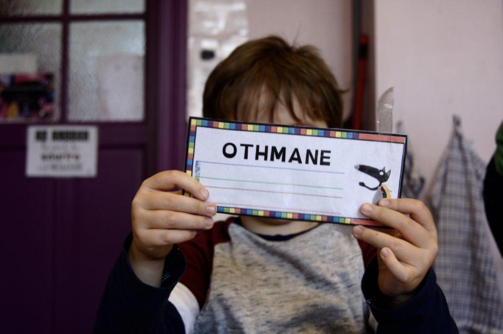 Othmane montre fièrement la petite pancarte avec son prénom.