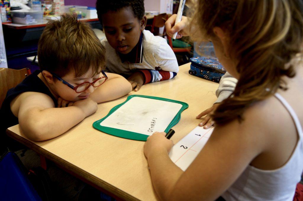Othmane travaille en groupe avec d'autres élèves et est très attentif.