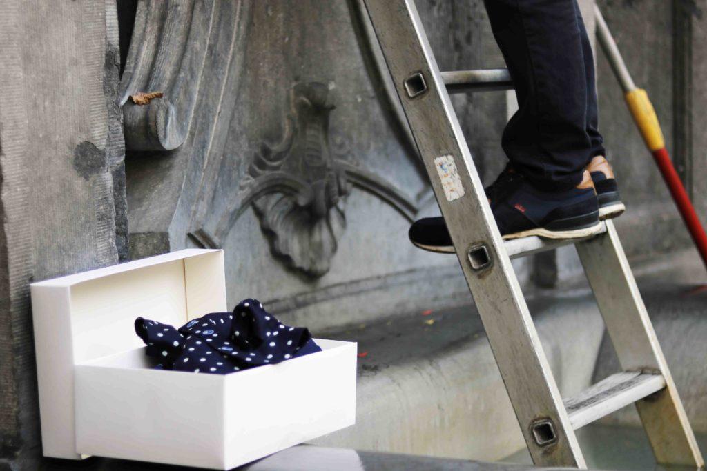 Nicolas doit monter sur une échelle dans l'eau pour atteindre la statue