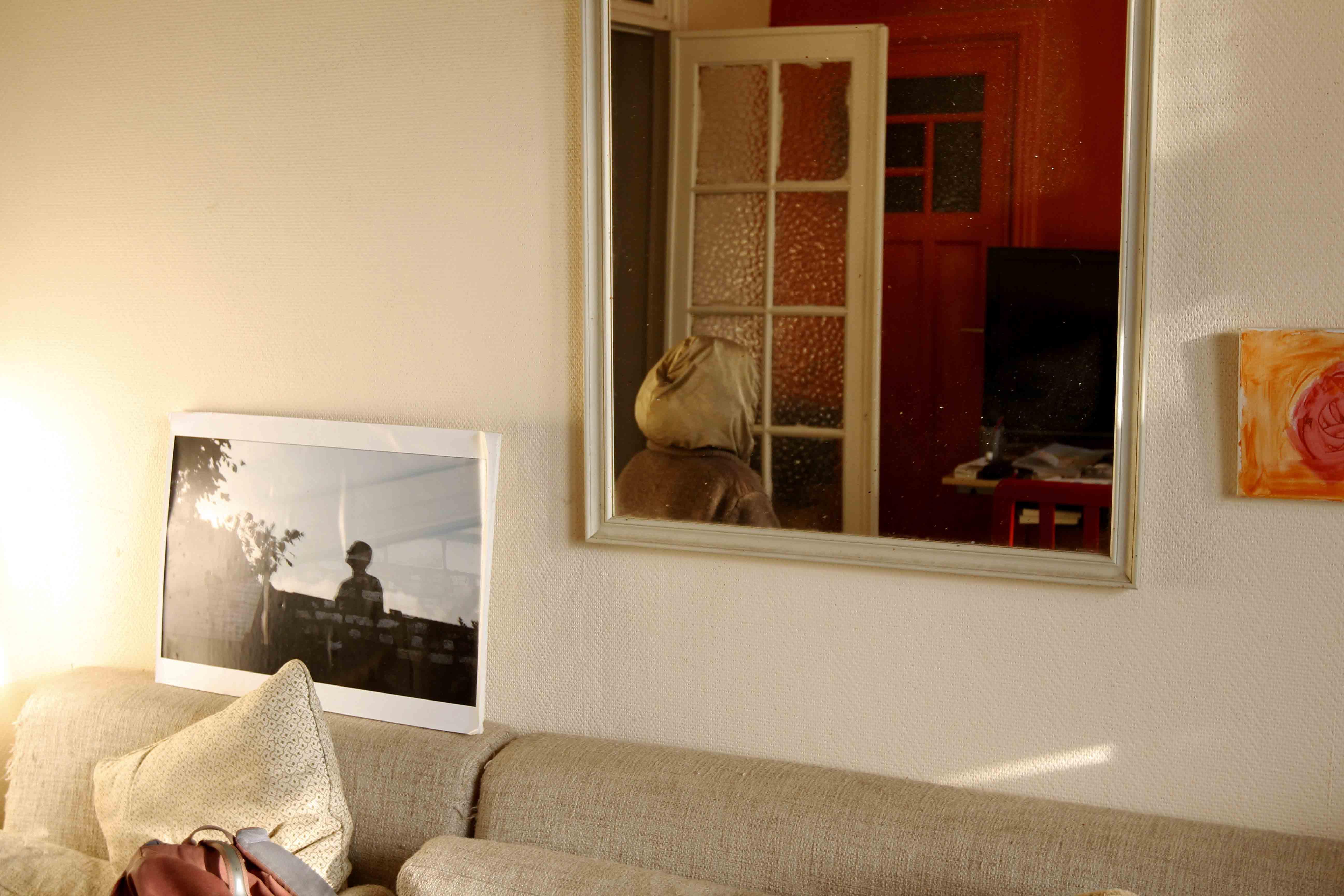 Salon et un miroir dans lequel on aperçoit Kristien, de dos.