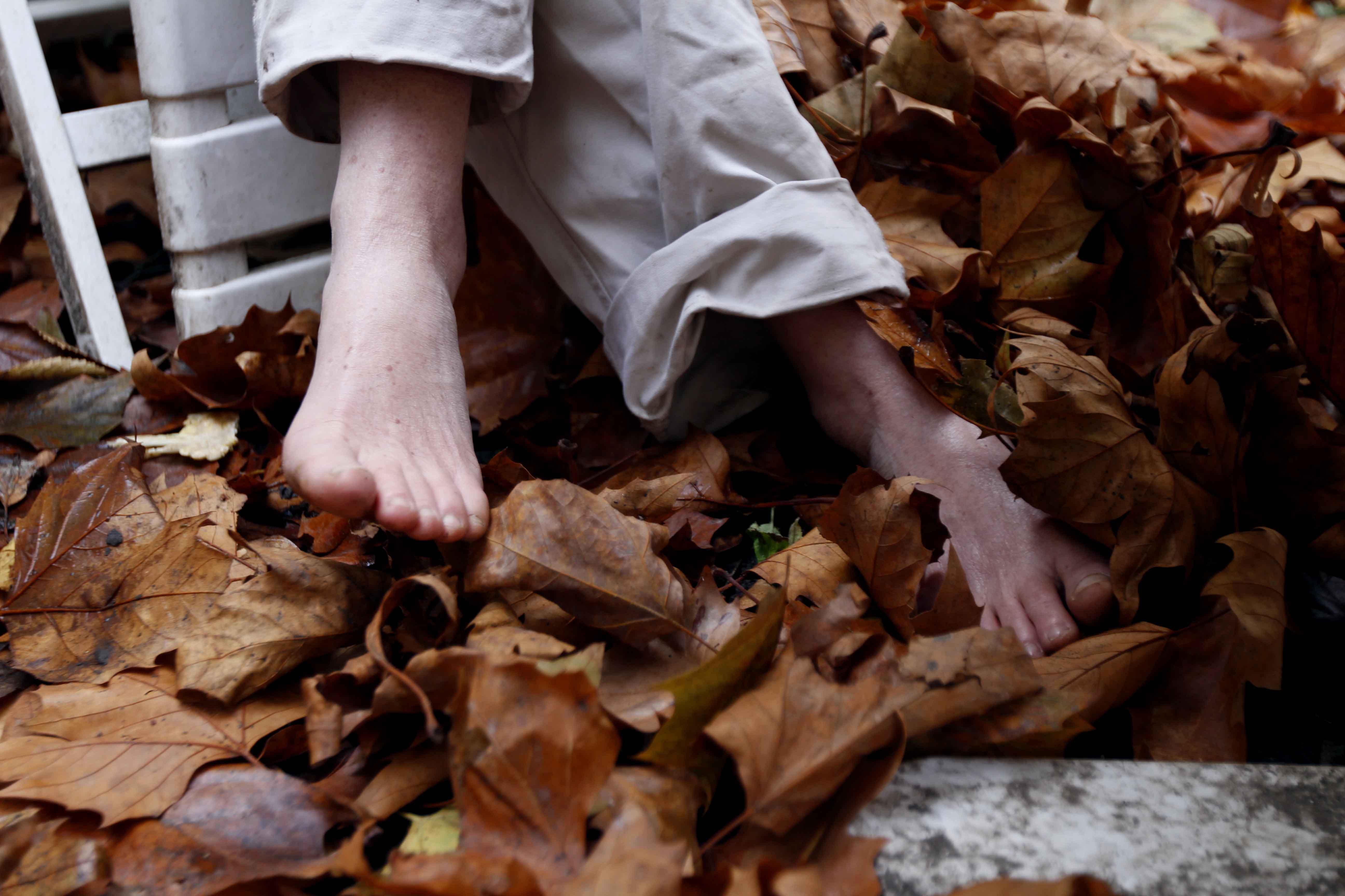 Pieds de Kristien dans les feuilles mortes de son jardin