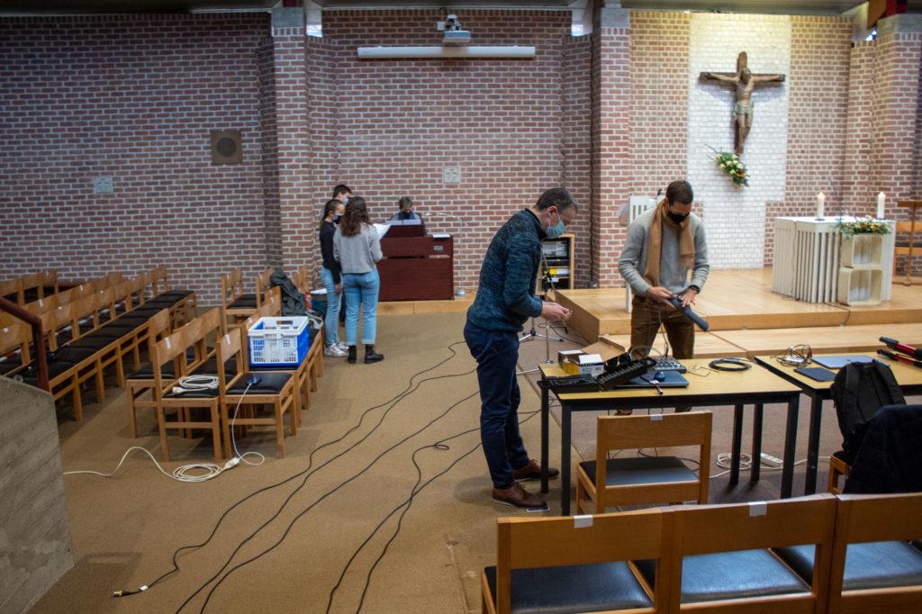 techniciens préparant la régie , déroulant les cables. La chorale répète au fond
