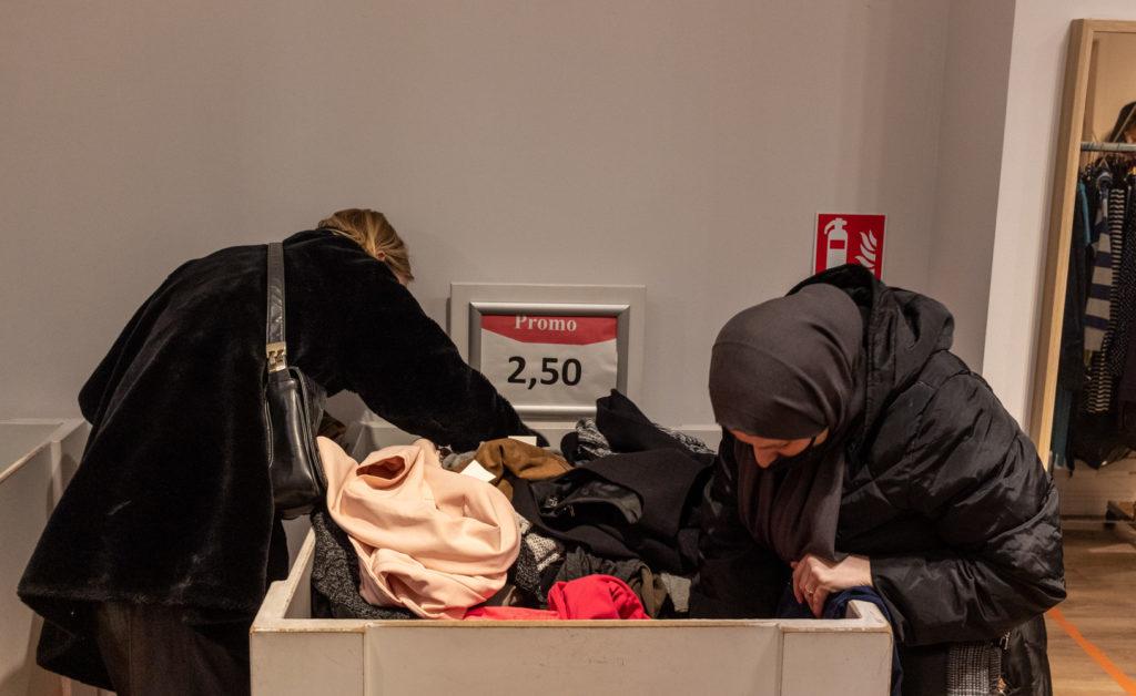 Dames fouillant un bac à la recherche de vêtements.