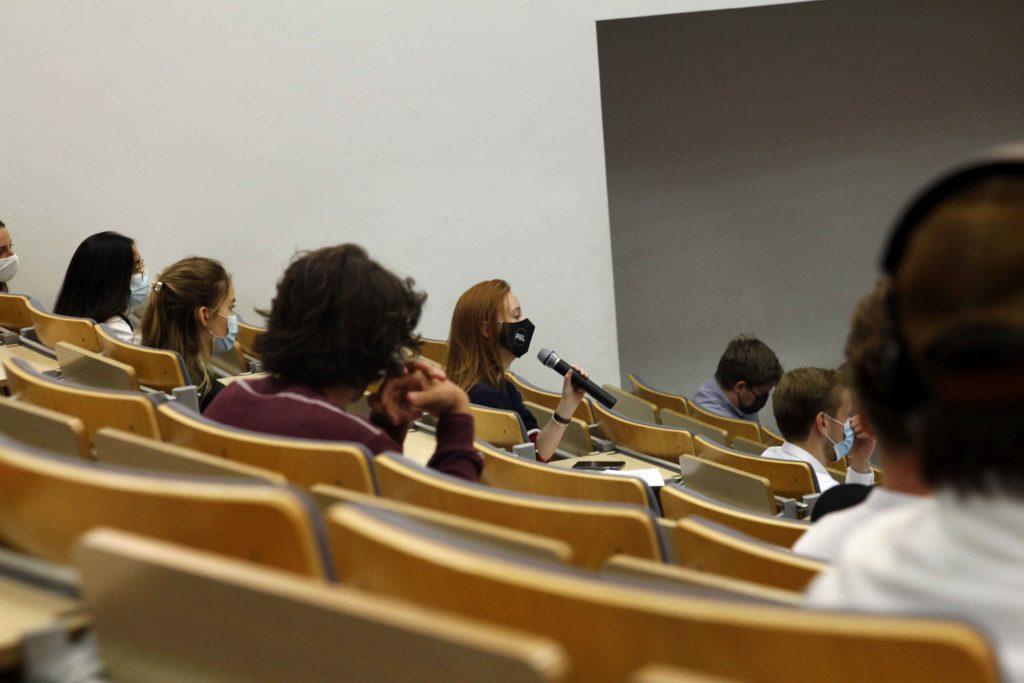 Étudiante assise dans un auditoire pose une question dans une micro
